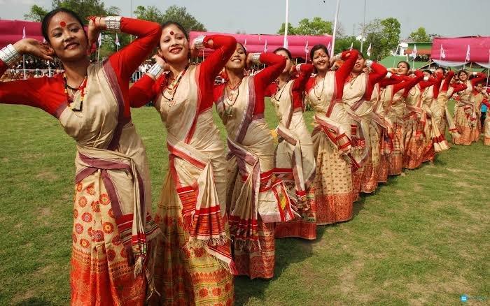 Assamese bihu dancers wearing muga mekhela and muga reeha